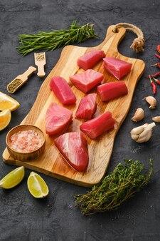 Pezzi freschi di filetto di tonno con spezie ed erbe aromatiche sul tagliere di legno
