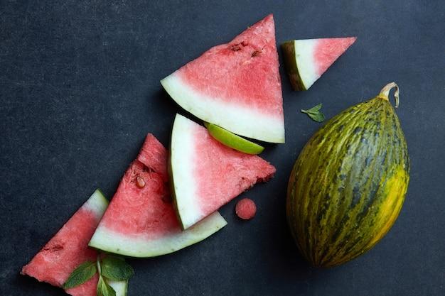 Pezzi freschi di anguria e melone su uno sfondo nero
