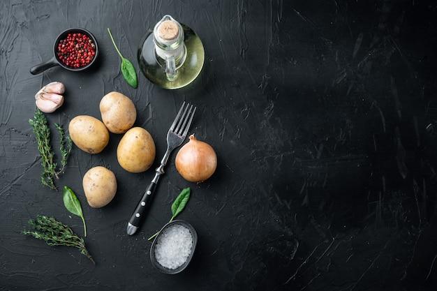Pila fresca di patate insieme, su sfondo nero, vista dall'alto laici piatta, con spazio per il testo copyspace