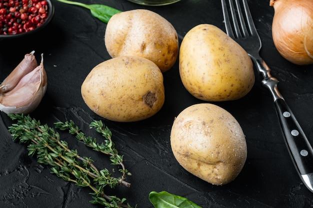 Pila fresca di set di patate, su sfondo nero