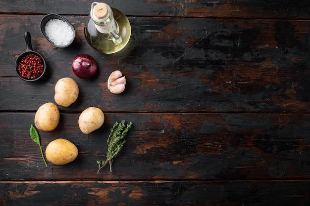 Pila fresca di patate insieme, sul vecchio fondo di tavolo in legno scuro, vista dall'alto laici piatta, con spazio per il testo copyspace