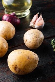 Mucchio fresco di patate insieme, sul vecchio fondo di tavolo in legno scuro