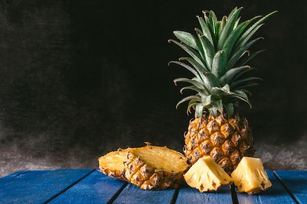 Frutta fresca dell'ananas sulla tavola di legno blu con fondo nero. copia spazio