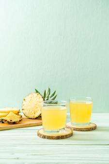 Succo di ananas fresco su uno sfondo di legno
