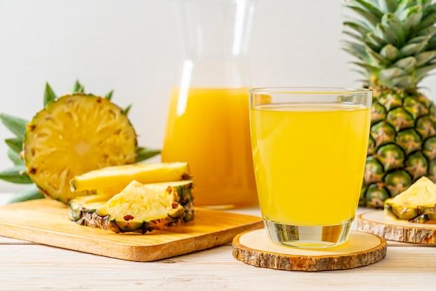 Succo di ananas fresco sulla superficie del legno