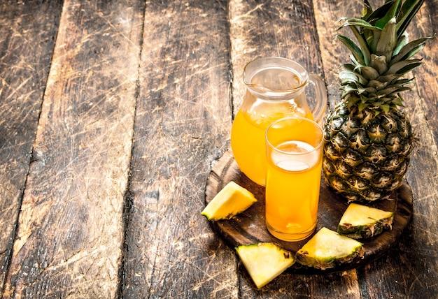 Succo di ananas fresco sulla tavola di legno.