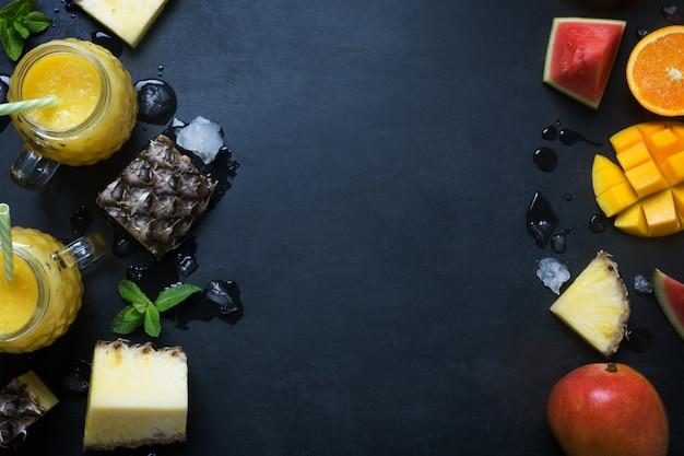 Frullato fresco del mango e dell'ananas in vetri con i frutti su un fondo rustico nero con lo spazio della copia