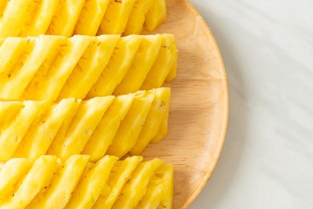 Ananas fresco affettato su piatto di legno Foto Premium