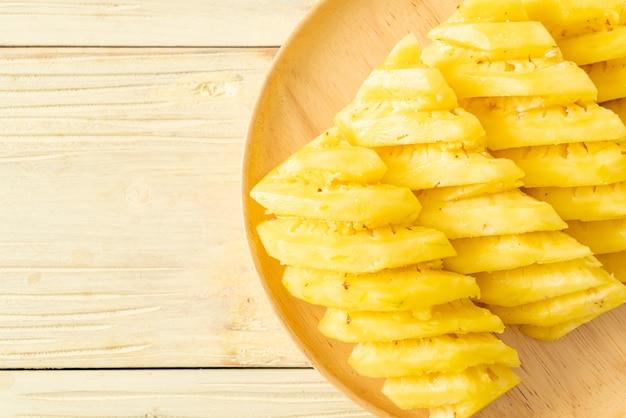 Ananas fresco affettato su piatto di legno