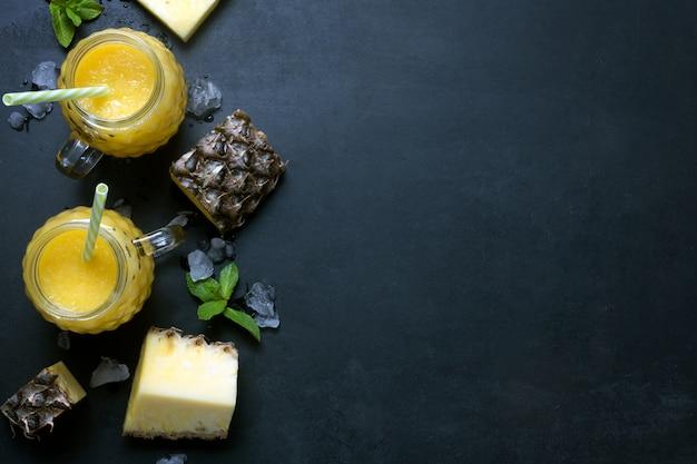 Frullato di ananas fresco in bicchieri con frutti su uno sfondo nero rustico. distesi e copia spazio con ghiaccio fuso
