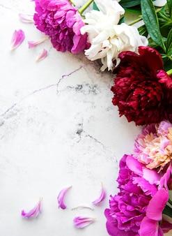 Confine di fiori di peonia rosa fresca con copia spazio su sfondo bianco marmo, piatto laici.