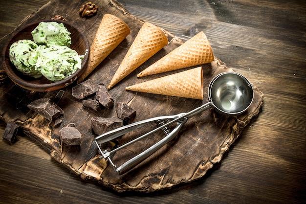 Gelato al pistacchio fresco in una ciotola con tazze di cialda su un tavolo di legno
