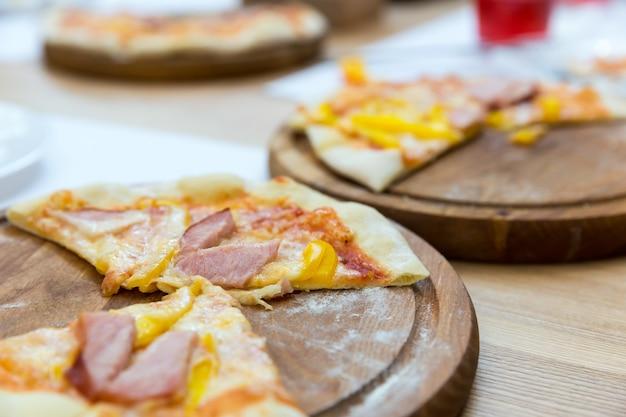 Pizza fresca su un primo piano del supporto di legno