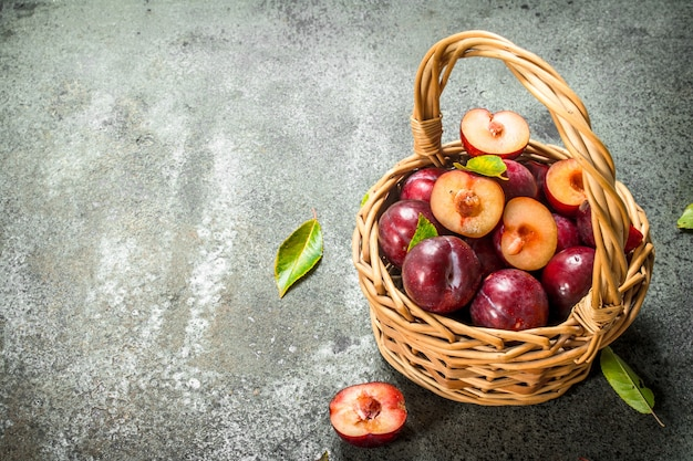 Prugne fresche in un cesto con foglie. su fondo rustico.