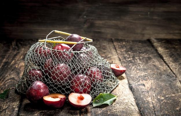 Prugne fresche in un sacchetto a rete. su uno sfondo di legno.
