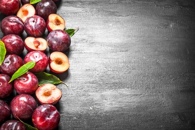 Prugne fresche con foglie. sulla lavagna nera.