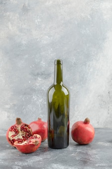 Frutti di melograno freschi con una bottiglia di vino su sfondo marmo.
