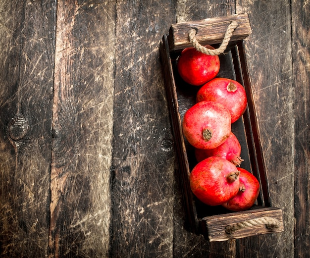 Melograni freschi in una vecchia scatola su uno sfondo di legno