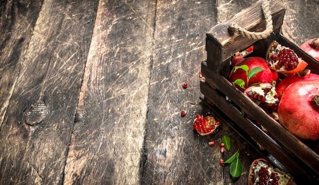 Melograni freschi in una vecchia scatola. su un tavolo di legno.