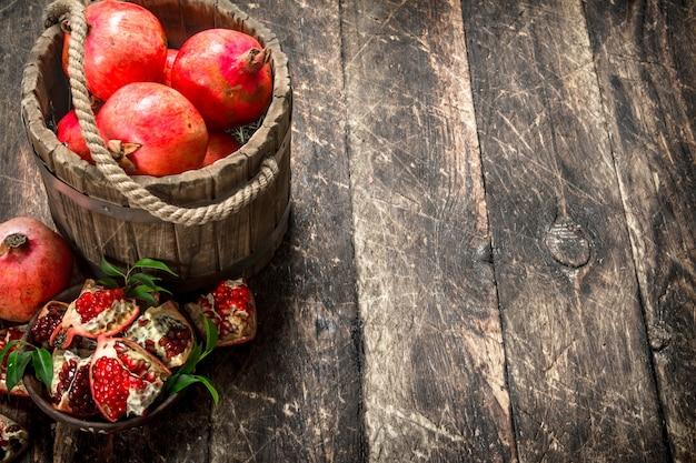 Melograni freschi nel secchio di legno su uno sfondo di legno