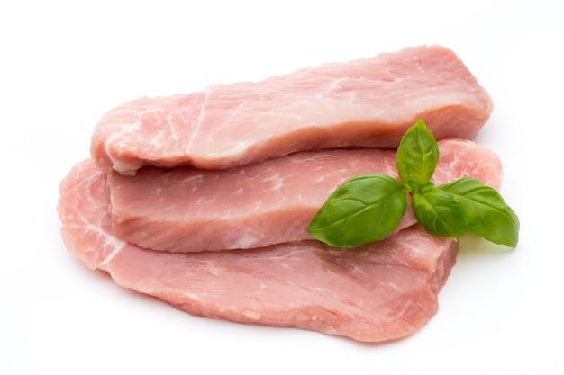 Filetto di maiale fresco con basilico su uno sfondo bianco.