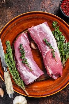 Carne di filetto di maiale fresco con rosmarino e timo. sfondo scuro. vista dall'alto.