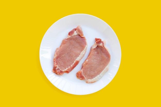 Carne di maiale fresca in piatto bianco su sfondo giallo.