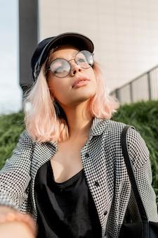 Ritratto fresco di una bella ragazza hipster con un viso di bellezza naturale con occhiali rotondi in abito casual alla moda seduto sull'erba per strada
