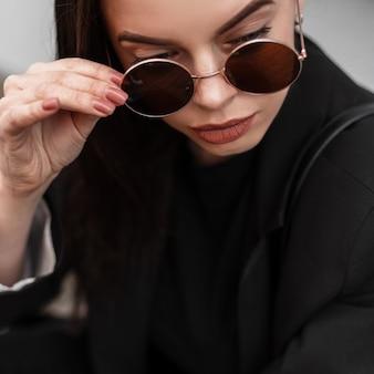 Ritratto fresco bella giovane donna con labbra sexy con pelle pulita sana in blazer alla moda in occhiali da sole rotondi vicino edificio in legno in città. la ragazza alla moda raddrizza gli occhiali alla moda all'aperto.