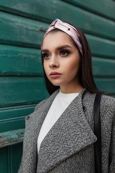 Giovane donna affascinante del ritratto fresco con le labbra sexy con trucco di bellezza in vestiti alla moda casuali della molla vicino alla parete di legno verde dell'annata nel giorno di primavera in città. attraente ragazza di moda cammina per strada.