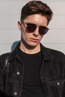 Giovane fresco ritratto fresco con l'acconciatura in giacca di jeans nera alla moda in occhiali da sole alla moda