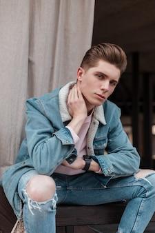 Giovane europeo alla moda ritratto fresco con acconciatura alla moda in elegante giacca blu denim con colletto bianco in posa sulla strada in città il giorno d'estate. modello di moda urbano di bell'aspetto ragazzo all'aperto