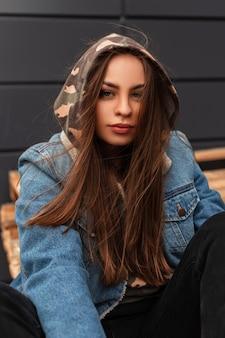 Fresco ritratto alla moda giovane donna in cappuccio militare in elegante giacca di jeans vintage blu vicino all'edificio grigio all'aperto. la modella americana della ragazza carina sta riposando per strada in città.