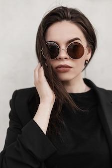 Fresco ritratto moderno giovane donna con capelli castani con labbra sexy con bella pelle pulita in occhiali da sole alla moda alla moda in blazer nero alla moda vicino al muro bianco vintage sulla strada in città. ragazza adorabile.