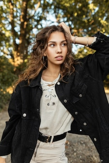 Il fresco ritratto di una bella giovane donna con i capelli ricci in jeans alla moda sembra in piedi nella natura. stile e bellezza primaverili femminili
