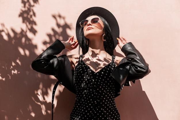 Fresco ritratto sexy giovane donna in cappello elegante in bel vestito in occhiali da sole alla moda in giacca di pelle nera vicino alla parete rosa all'ombra di un albero. gode di bella ragazza in abito alla moda
