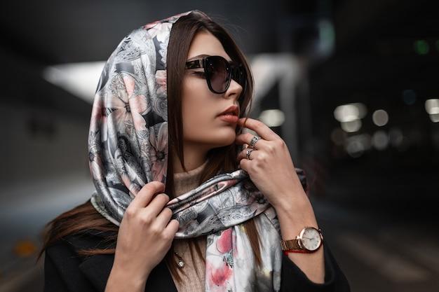 Ritratto fresco giovane donna attraente con pelle pulita sana con labbra sexy in occhiali da sole alla moda in cappotto con elegante sciarpa di seta sulla testa in città. modello di moda ragazza d'affari europea. stile retrò