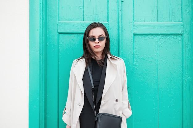 Ritratto fresco giovane bella donna in abiti primaverili alla moda in eleganti occhiali da sole retrò vicino alla porta di livido in legno vintage sulla strada in città. modello di moda ragazza moderna all'aperto. aspetto alla moda.