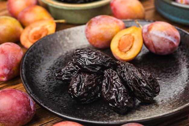 Prugne fresche e prugne secche su tavola di legno