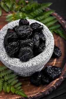 Prugne fresche in una ciotola di pietra. prugne secche su tavola di pietra scura. prugne cibi sani. prugne secche in ciotola.