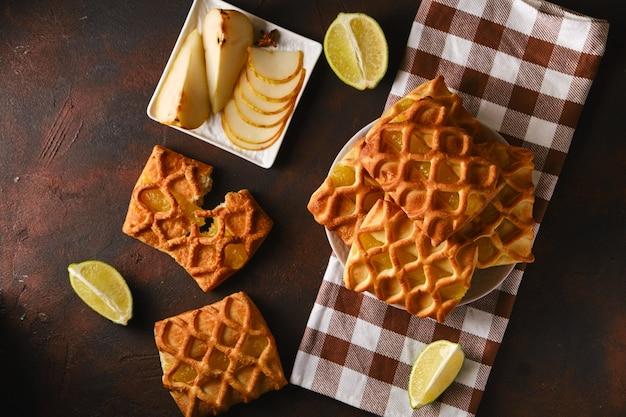 Mini torte di pasta sfoglia fresca con ripieno di marmellata di pere e lime su un tovagliolo a scacchi, fette di lime e pera a fette su un piattino su sfondo scuro, vista orizzontale dall'alto, flatlay