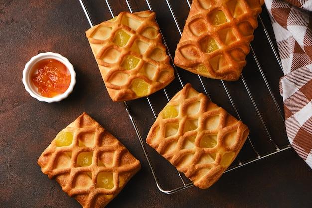 Mini torte di pasta sfoglia fresca con ripieno di marmellata di pere e lime su griglia per arrosti su sfondo scuro, vista orizzontale dall'alto, flatlay