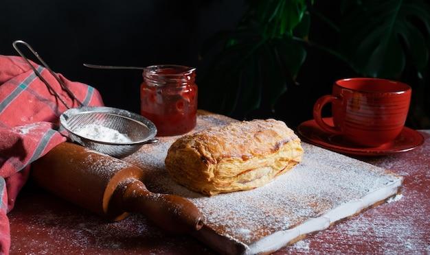 Fresh puff dotato di prugna o marmellata di ribes rosso sul tavolo con una tazza rossa e un barattolo di marmellata su sfondo nero.