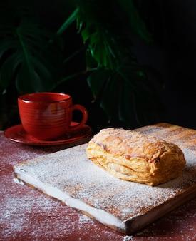 Soffio fresco sul tavolo con una tazza di caffè rossa su sfondo nero.