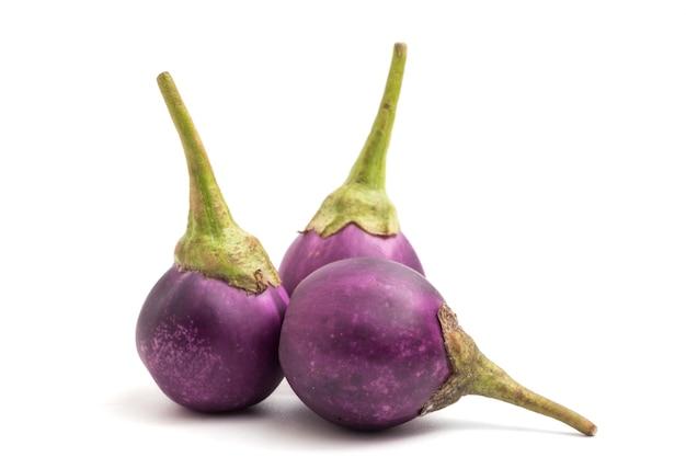 Melanzane viola fresche su fondo bianco.