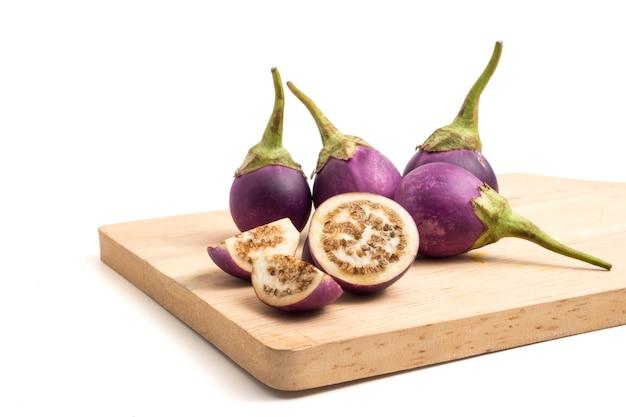 Melanzane viola fresche sul cassetto di legno sopra priorità bassa bianca.