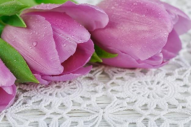 Tulipani viola freschi su una bellissima tovaglia all'uncinetto