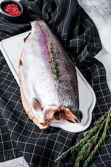 Pesce trota iridea fresco marinato con sale e timo. superficie grigia. vista dall'alto