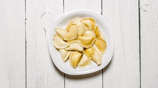 Ravioli freschi con formaggio nel piatto. su uno sfondo di legno bianco. vista dall'alto