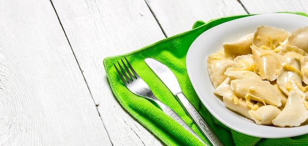Ravioli freschi con formaggio nel piatto. su uno sfondo di legno bianco.